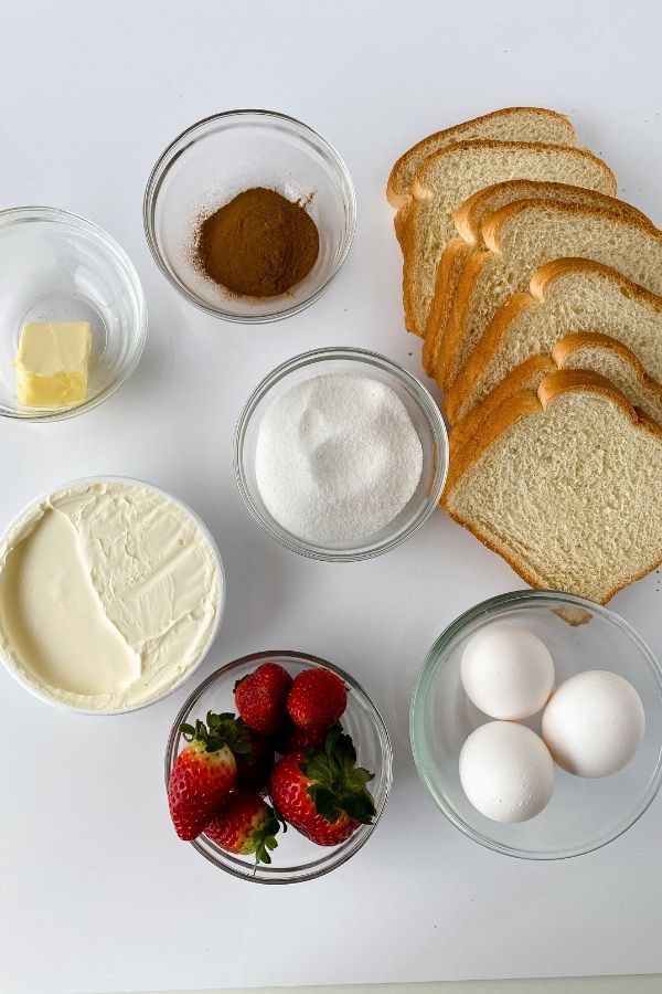 Bread, eggs, strawberries, butter and other ingredients need for stuffed french toast.