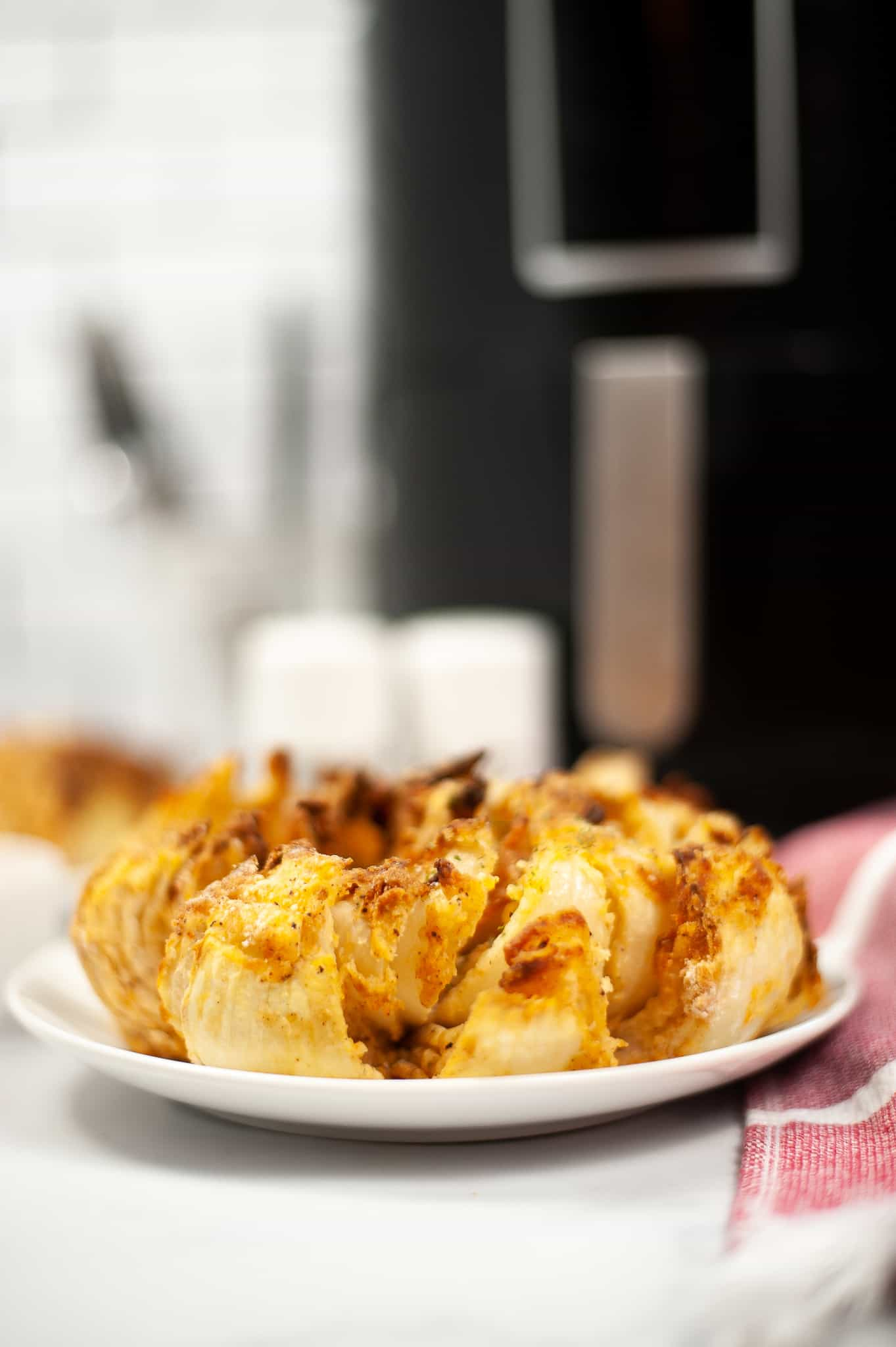 Side view of air fryer blooming onion on a white plate with air fryer and salt and pepper shakers in the background.