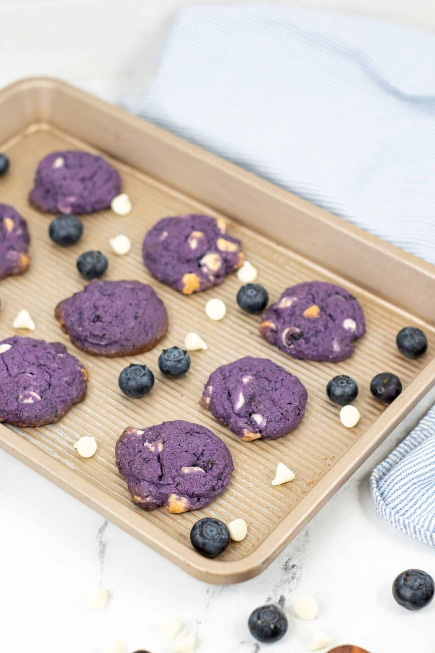 Cookie sheet with blueberry white chocolate cookies with blueberries and chips.