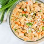 Top shot of a bowl of Buffalo Chicken Salad in a clear bowl with scallions on the side.
