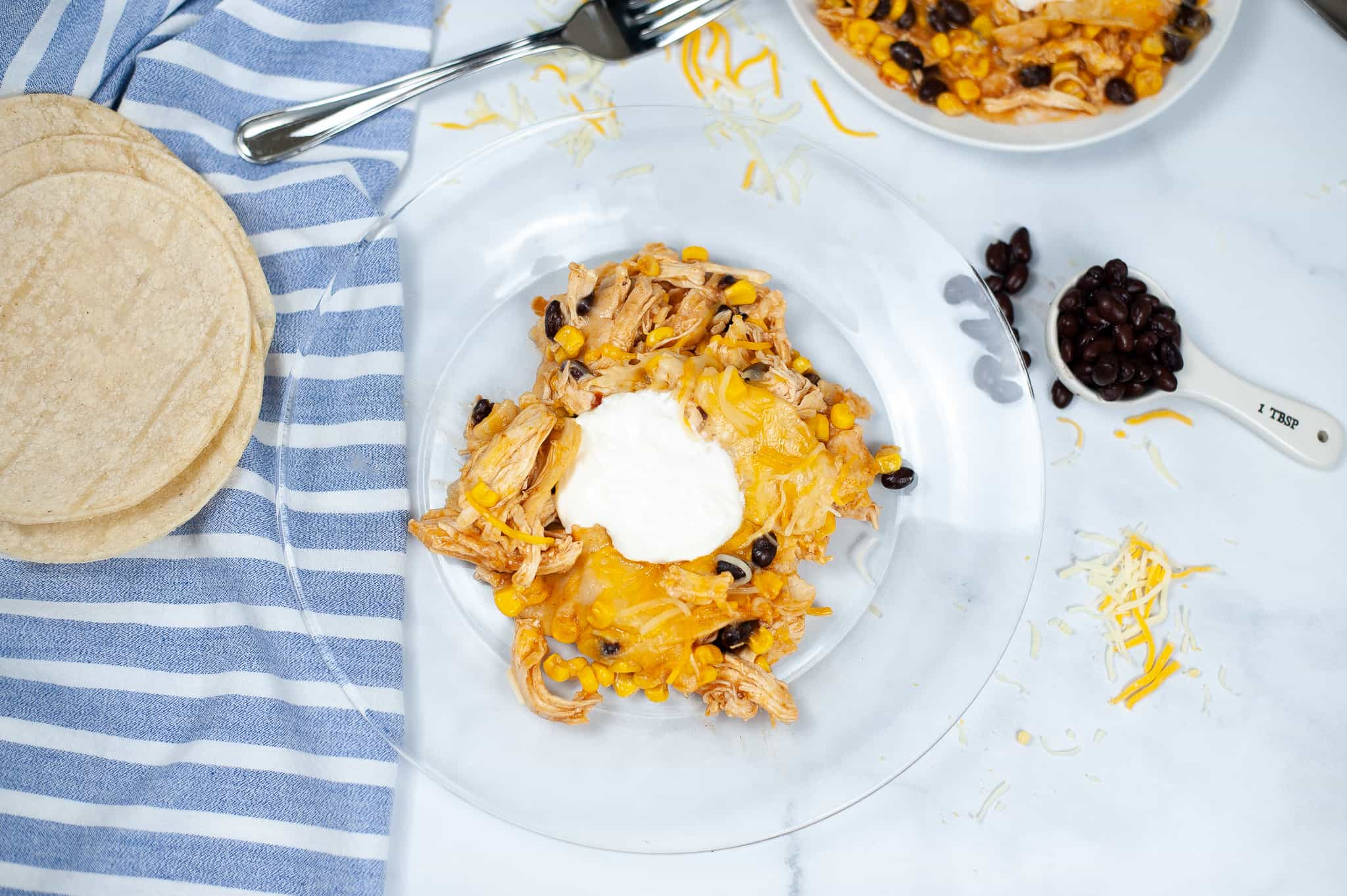 Top shot of crock pot enchiladas on a clear plate with a blue and white stripped napkin.
