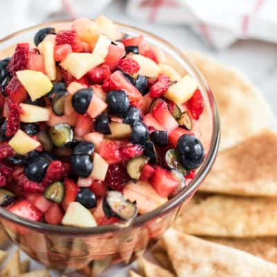 Side view of a clear dish of fruit salsa and cinnamon chips.