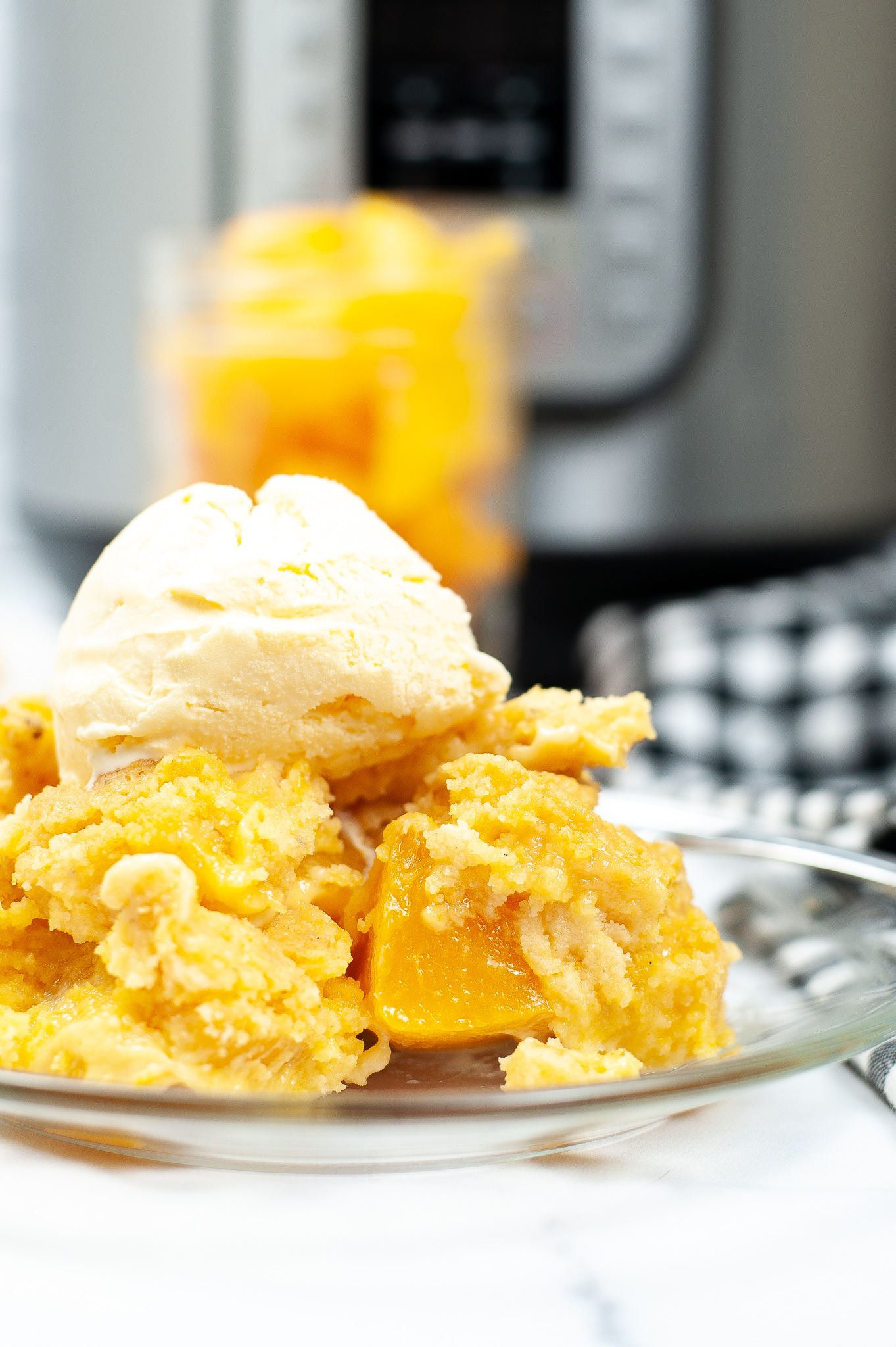 Close up side view of peach cobbler topped with ice cream.