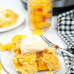 Peach cobbler on a clear plate with icecream and peaches in a jar in the background.