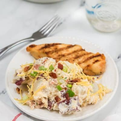 A serving of Loaded Potato salad on a white plate with a side of grilled chicken.