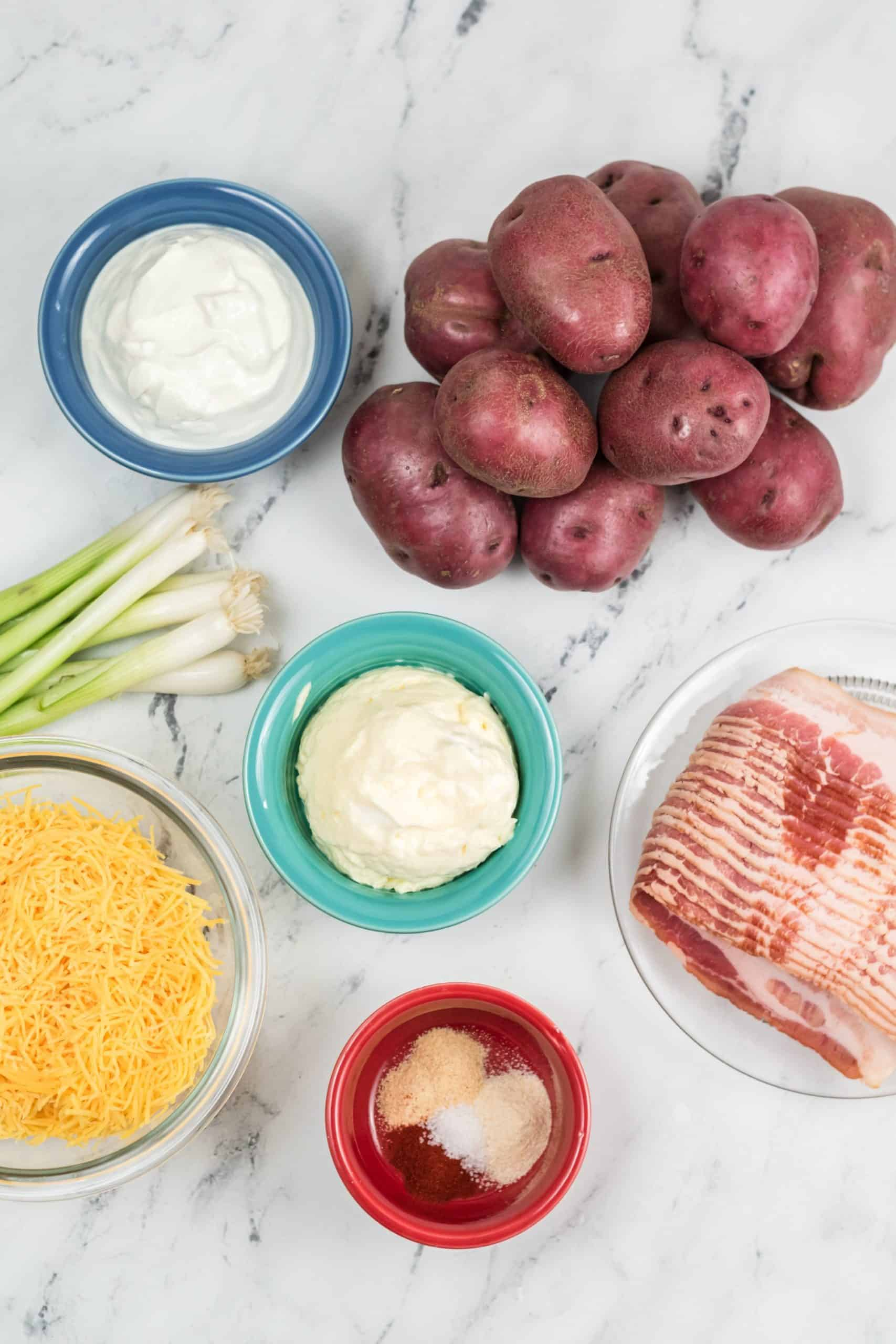 Potatoes scallions cheese bacon butter and sour cream in bowls.