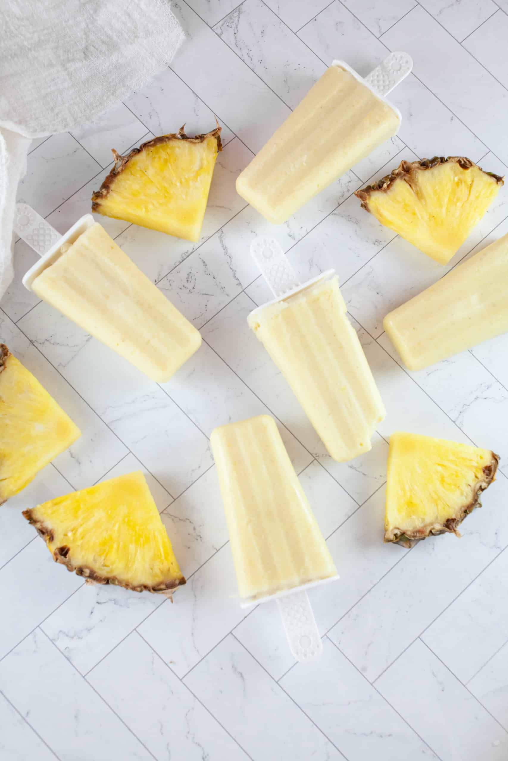 Slices of pineapple surround pina colada popsicles.