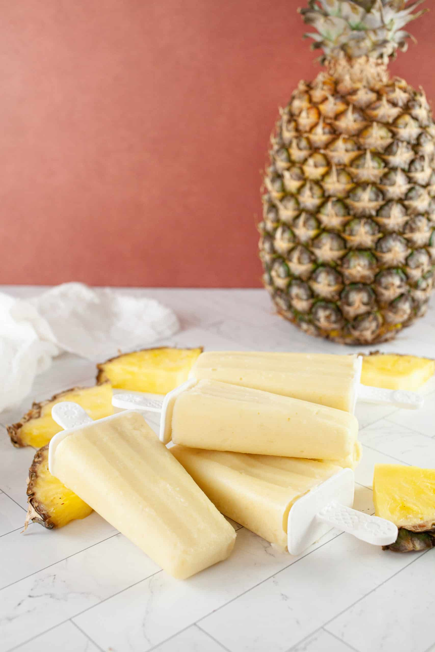 Pineapple on counter with pina colada pops and sliced pineapple.
