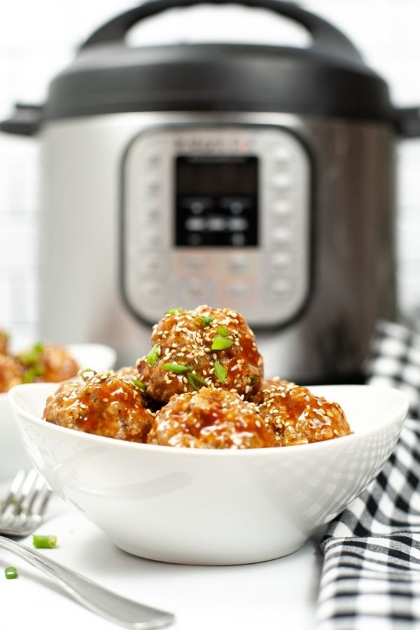 Side view of asian meatballs in a white bowl.