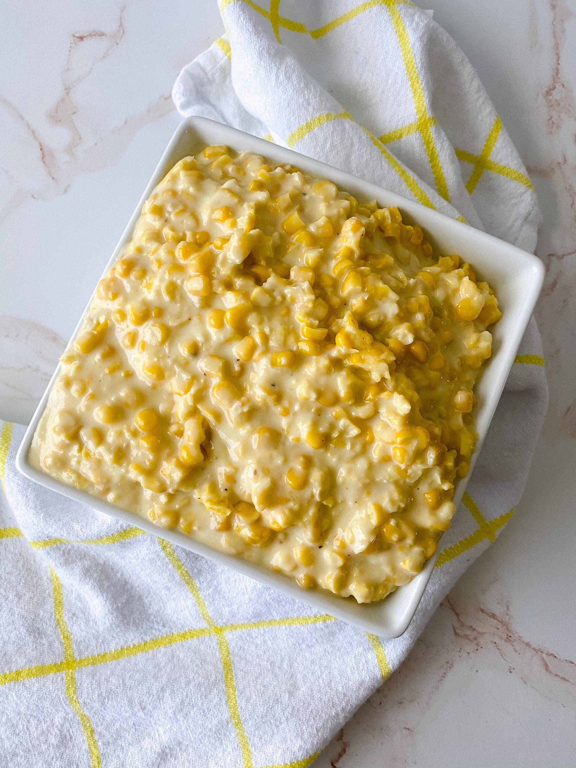Close up of a square white dish of cream style corn.