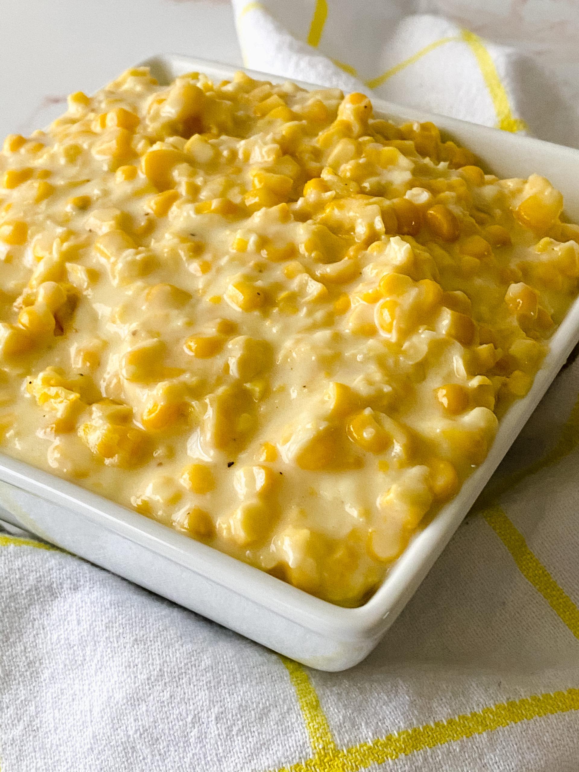 Side view of cream corn in a white square dish.