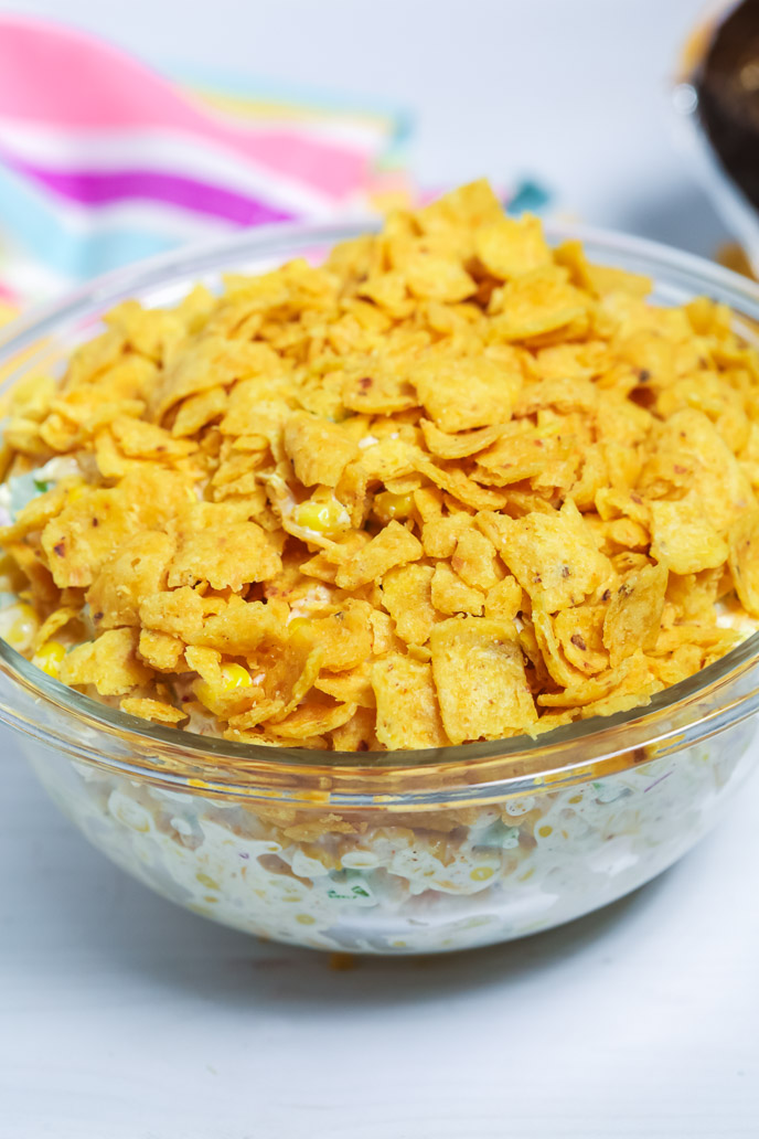 side view of frito corn salad in a clear glass bowl.