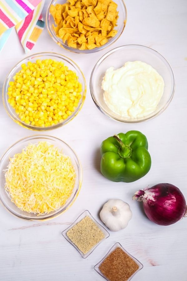 Clear glass bowls of cheese corn, sour cream and fresh vegetables to make corn salad.