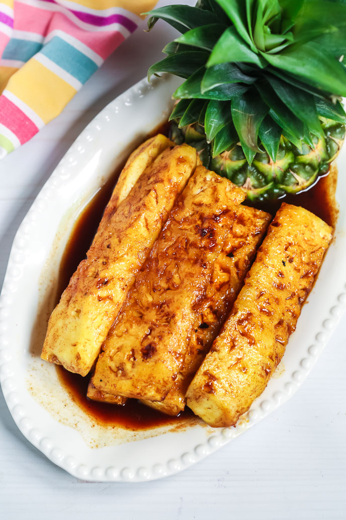 Grilled brazilian pineapple on a white plate with a striped napkin
