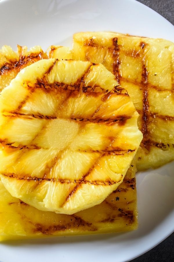 Grilled rounds of pineapple with cross hatch markings.
