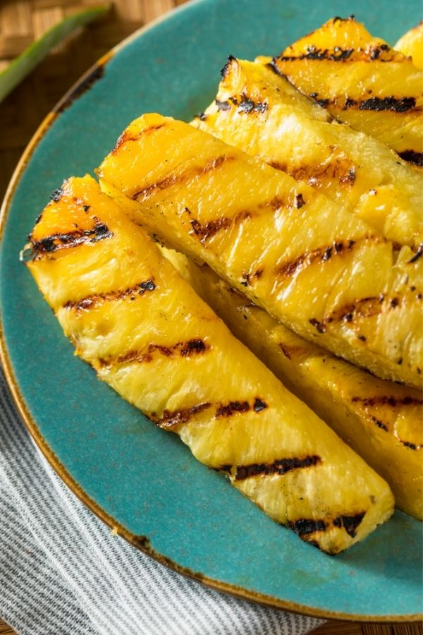 Close up on grilled pineapple wedges on an aqua plate.