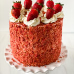 Strawberry Crunch cake on a cake stand.