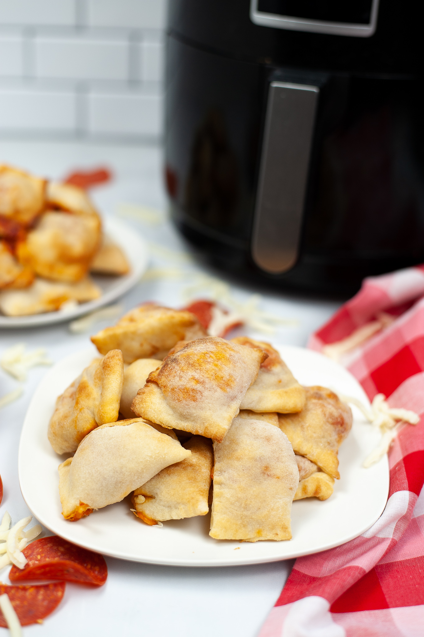 Stack of pizza rolls on a white plate.