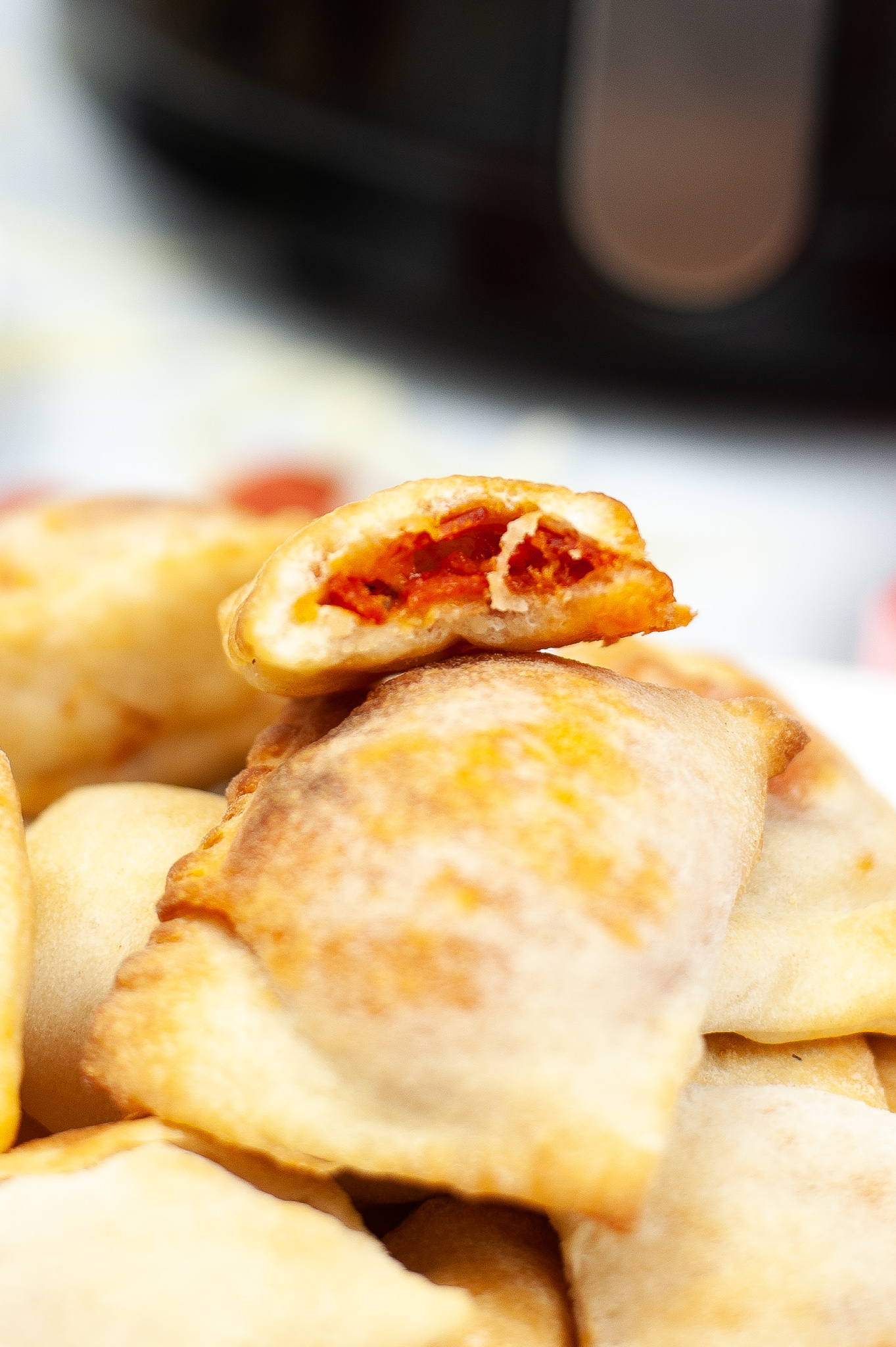 Picture of the inside of a pizza roll on top of a stack of other pizza rolls.