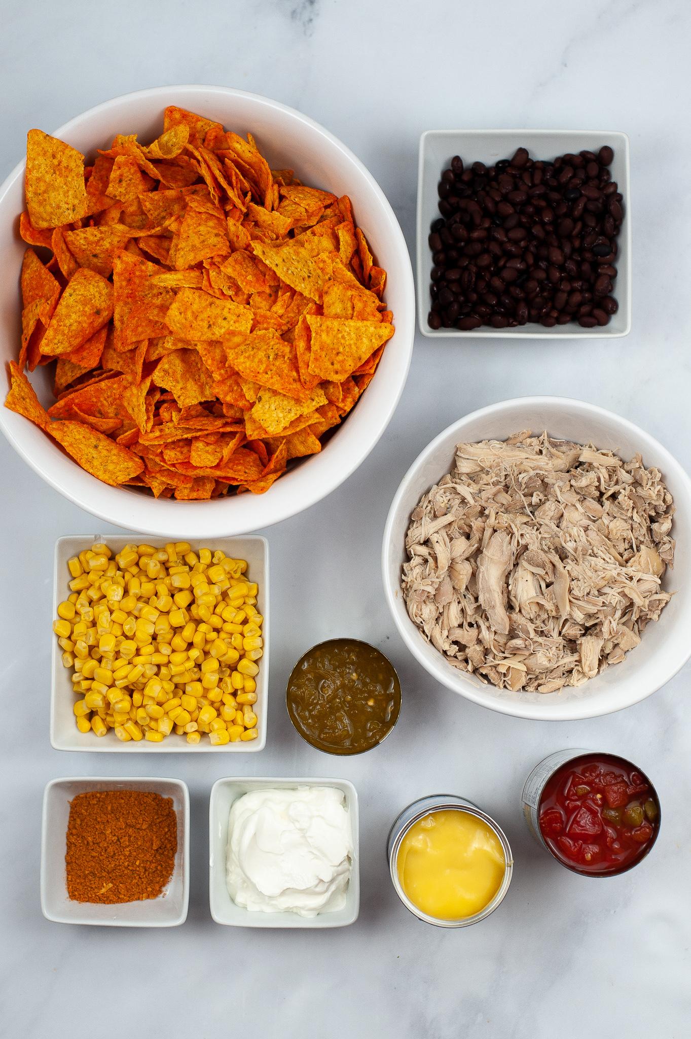 A bowl of doritos, corn, chicken and seasonings.