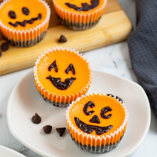 Mini Halloween Cheesecakes on a white plate with jack o lantern faces.