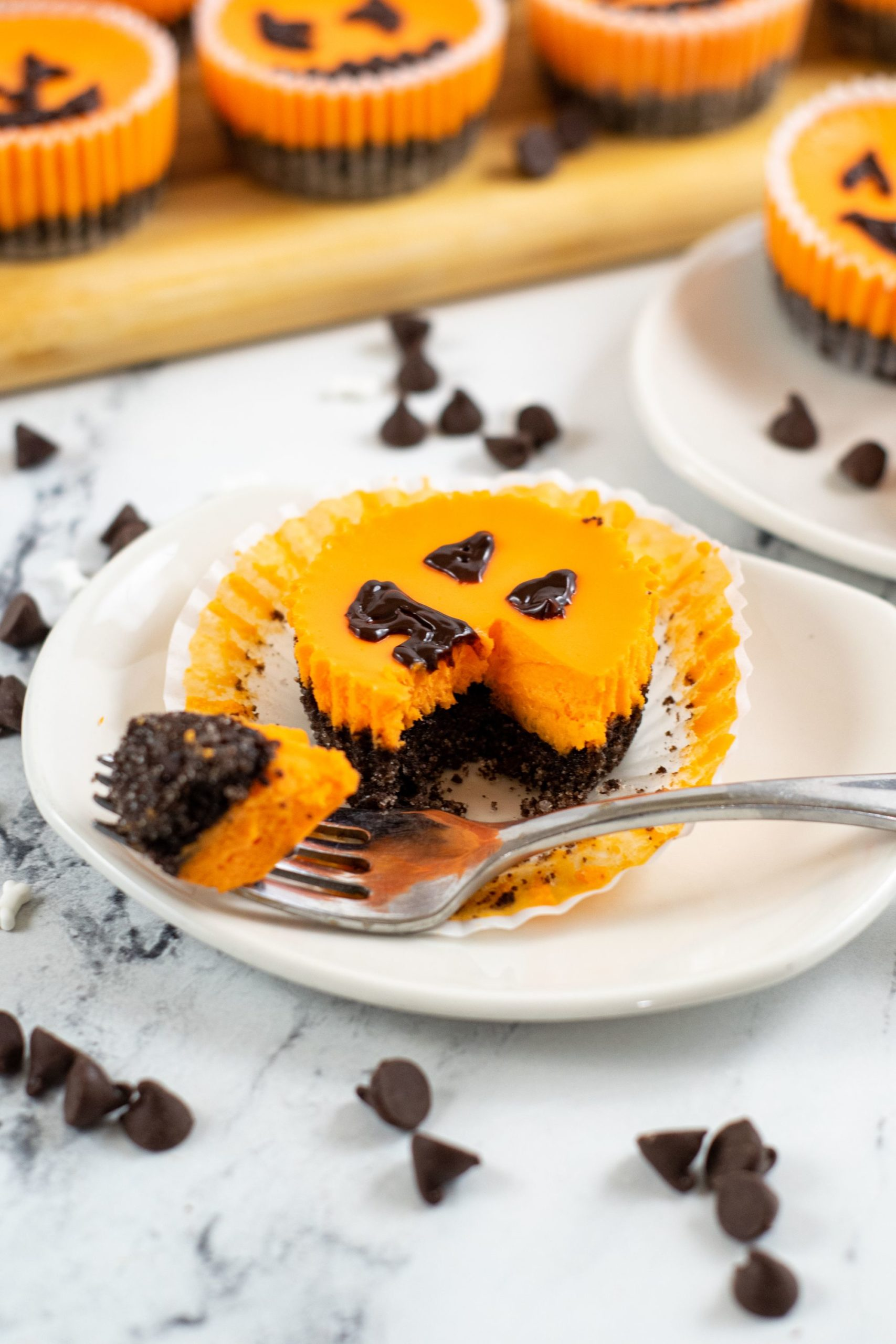 A white dish with a mini Halloween cheesecake on the plate with a fork full on the side.
