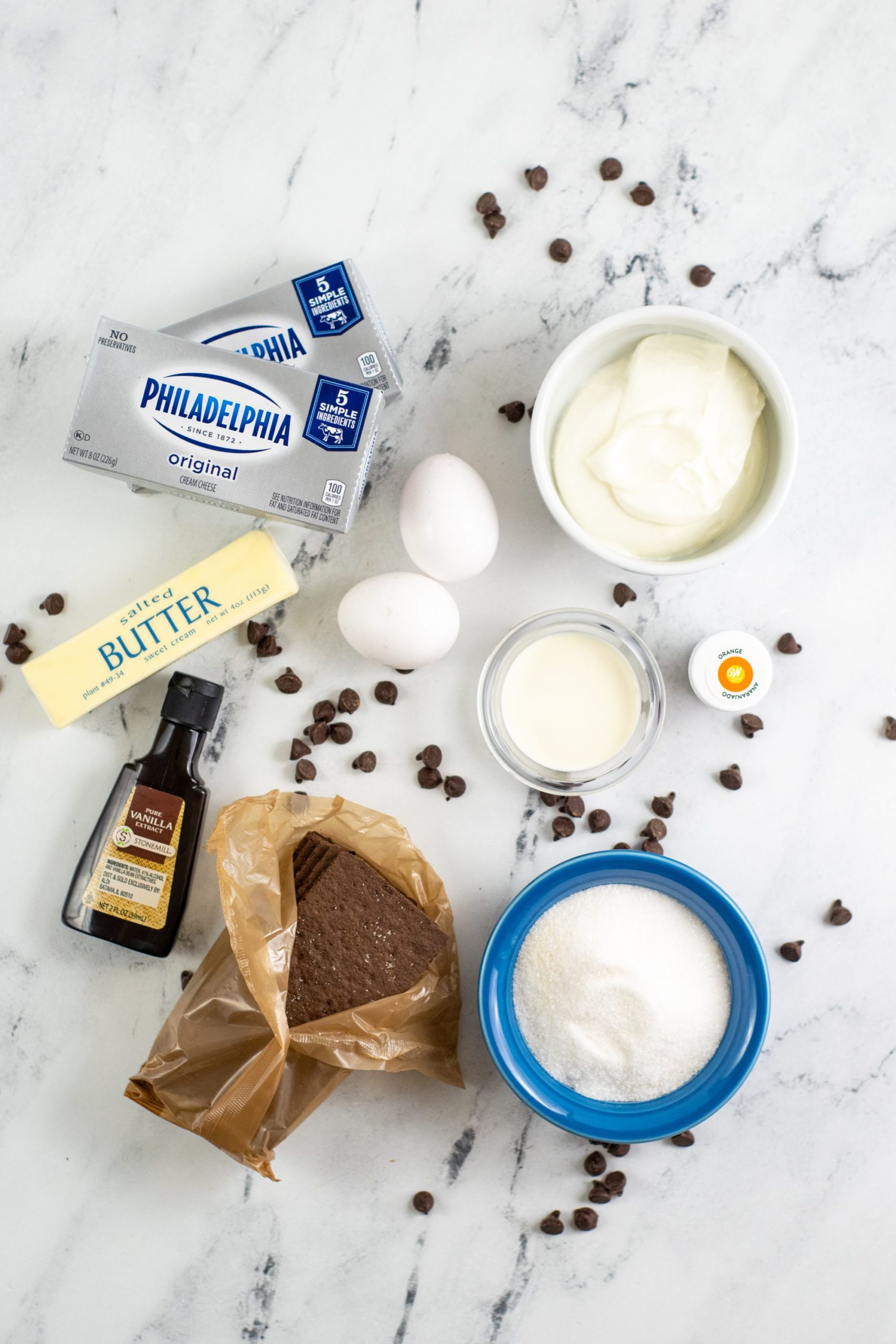 Butter, cream cheese, eggs, vanilla, flour and other ingredients needed to make cheesecake.