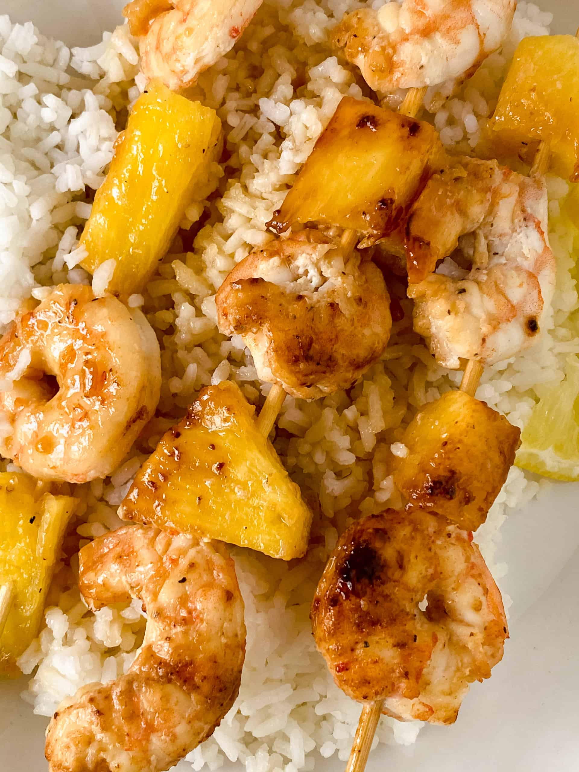 Close up on skewers with shrimp and pineapple.