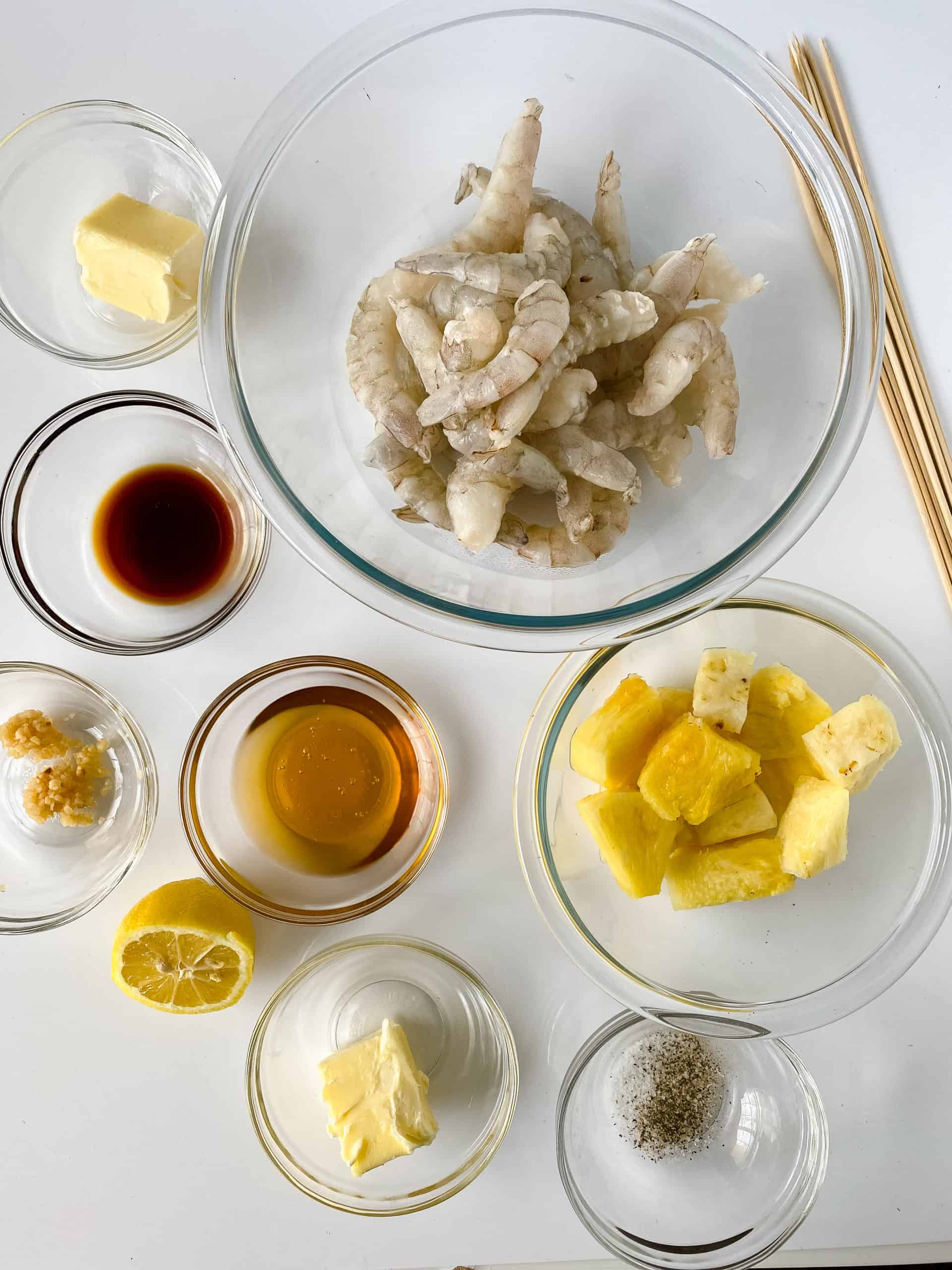 Clear glass bowls of shrimp, pineapple honey and other ingredients.