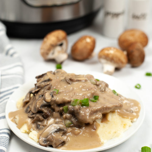 White plate of salisbury steak with the Instant Pot in the background.