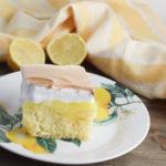Lemon Meringue poke cake on a white plate with lemons.