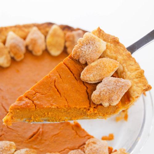 Slice of pumpkin pie on a server with whole pie beneath it.