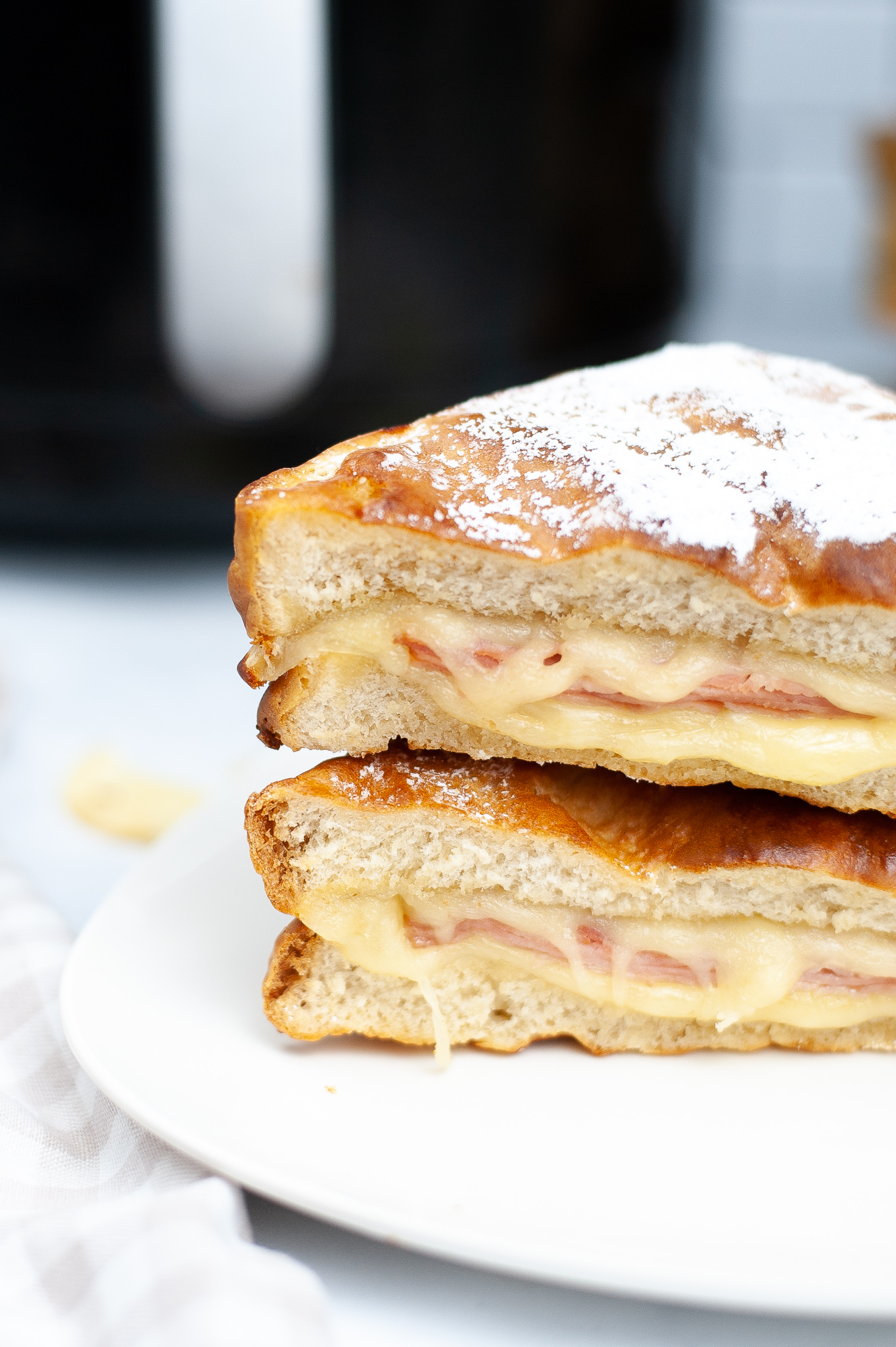 Side view of a stacked monte cristo sandwich on a plate.