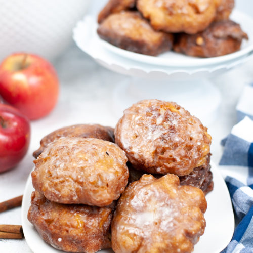 White dish of apple fritters with apples in the background.