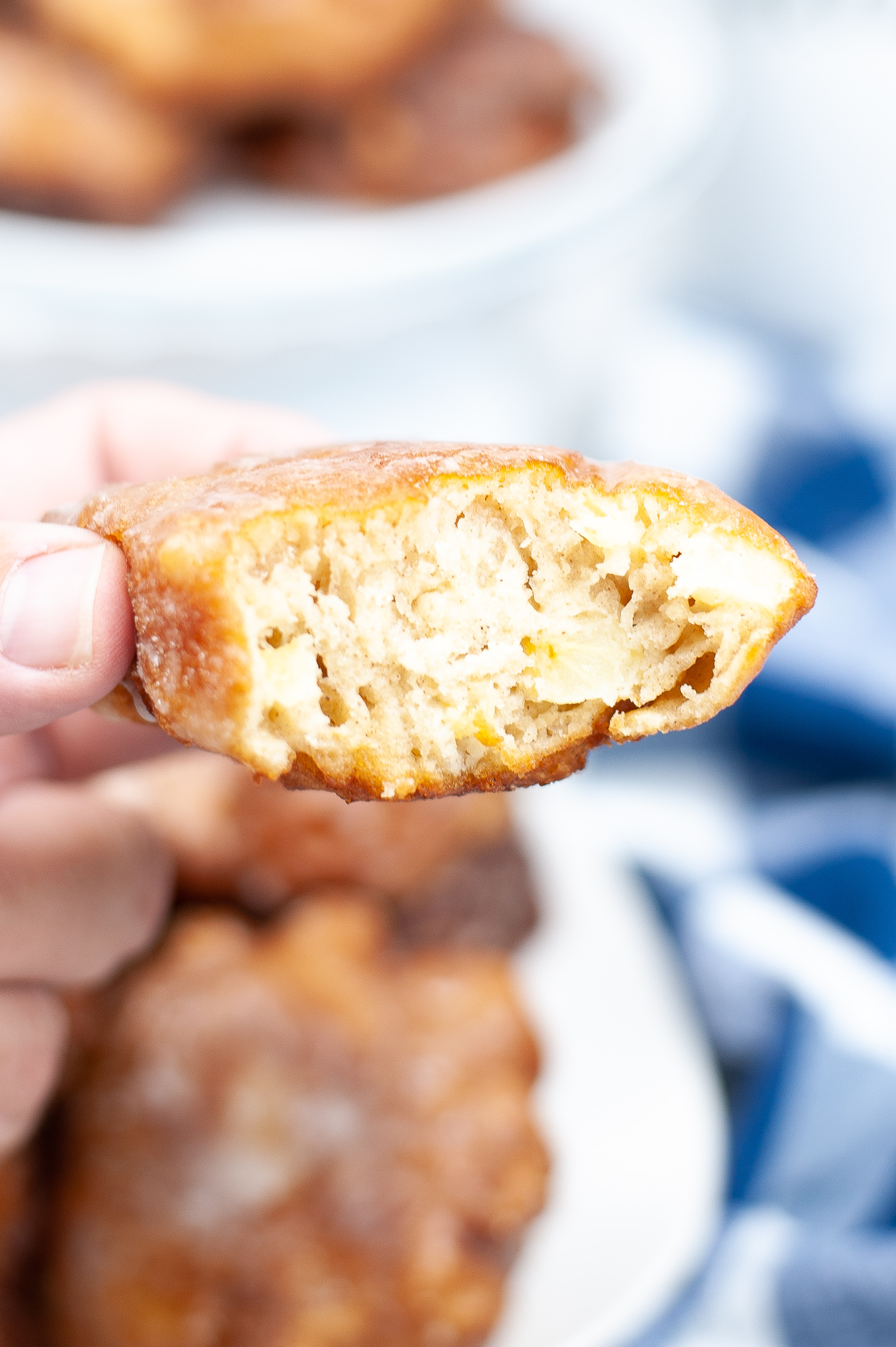 An apple fritter with a bite taken out in close up.