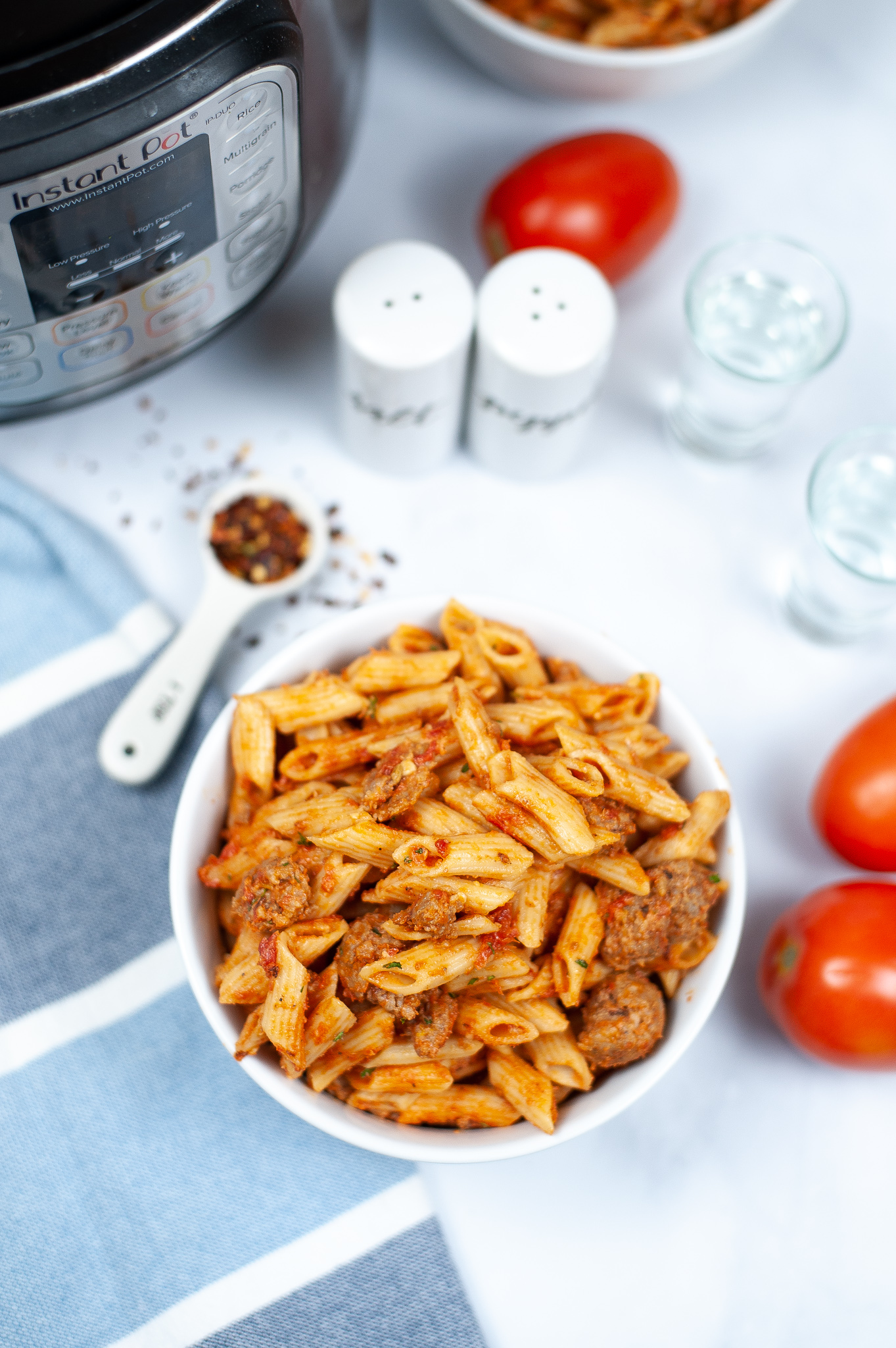 White bowl of penne vodka sauce with tomatoes and seasonings  on the side.
