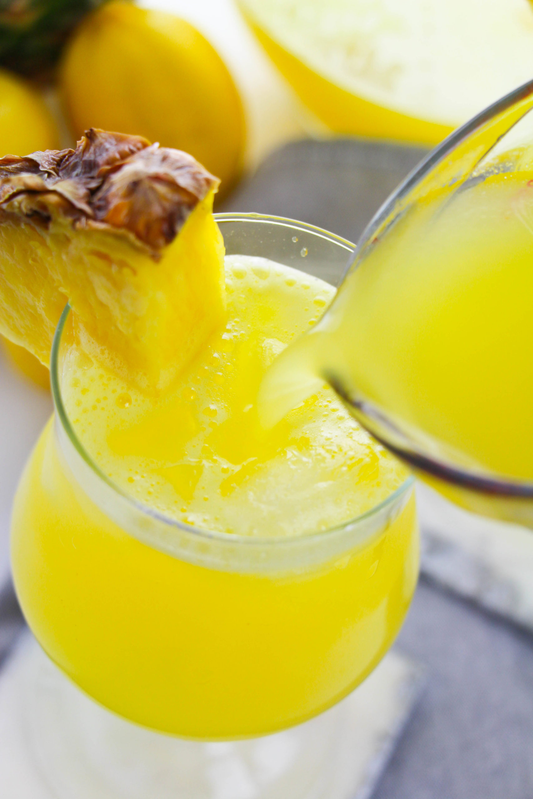 Side view of a glass of pineapple lemonade with a piece of pineapple on the glass.
