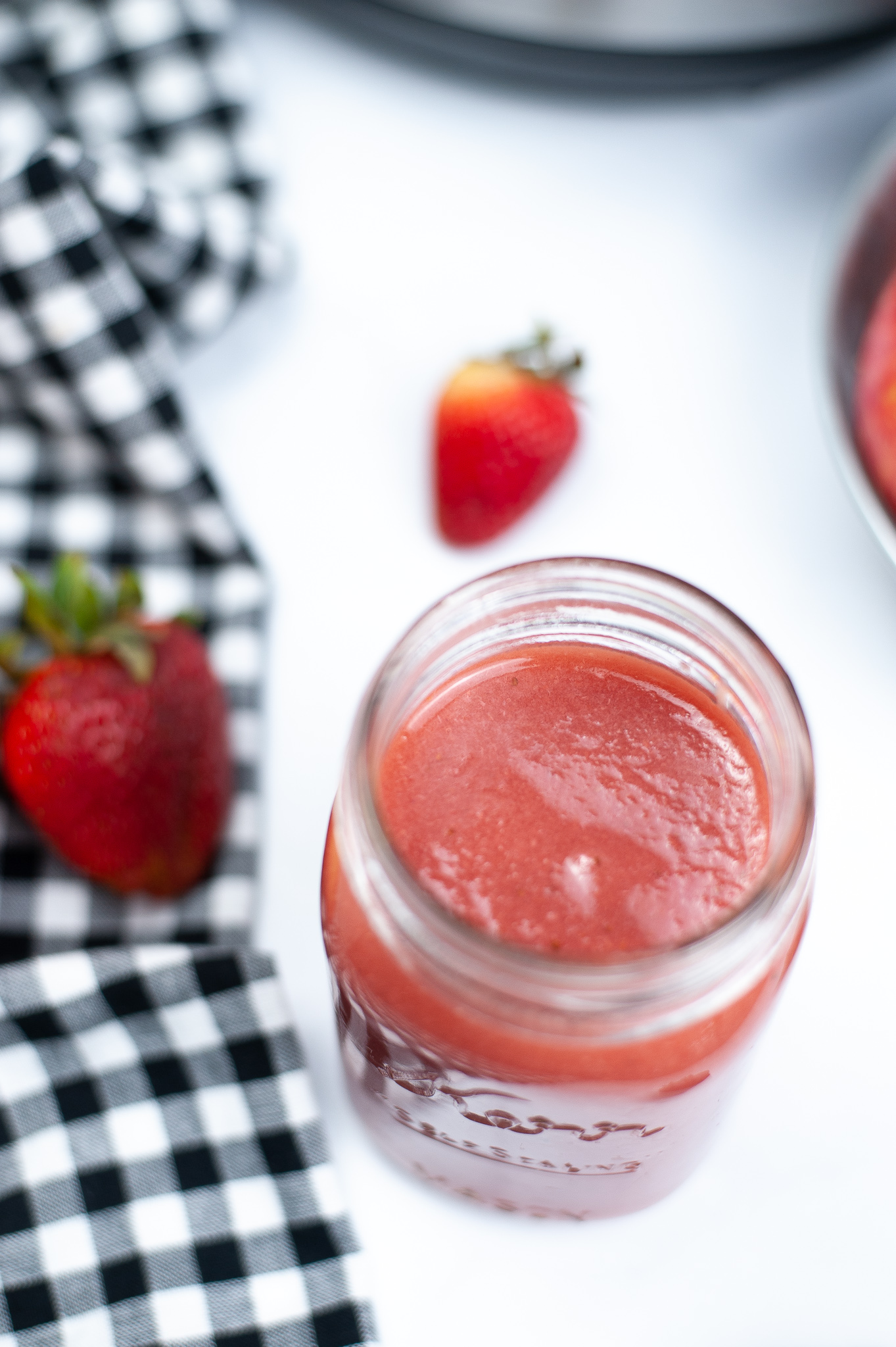 Top shot of strawberry applesauce surrounded by whole strawberries.