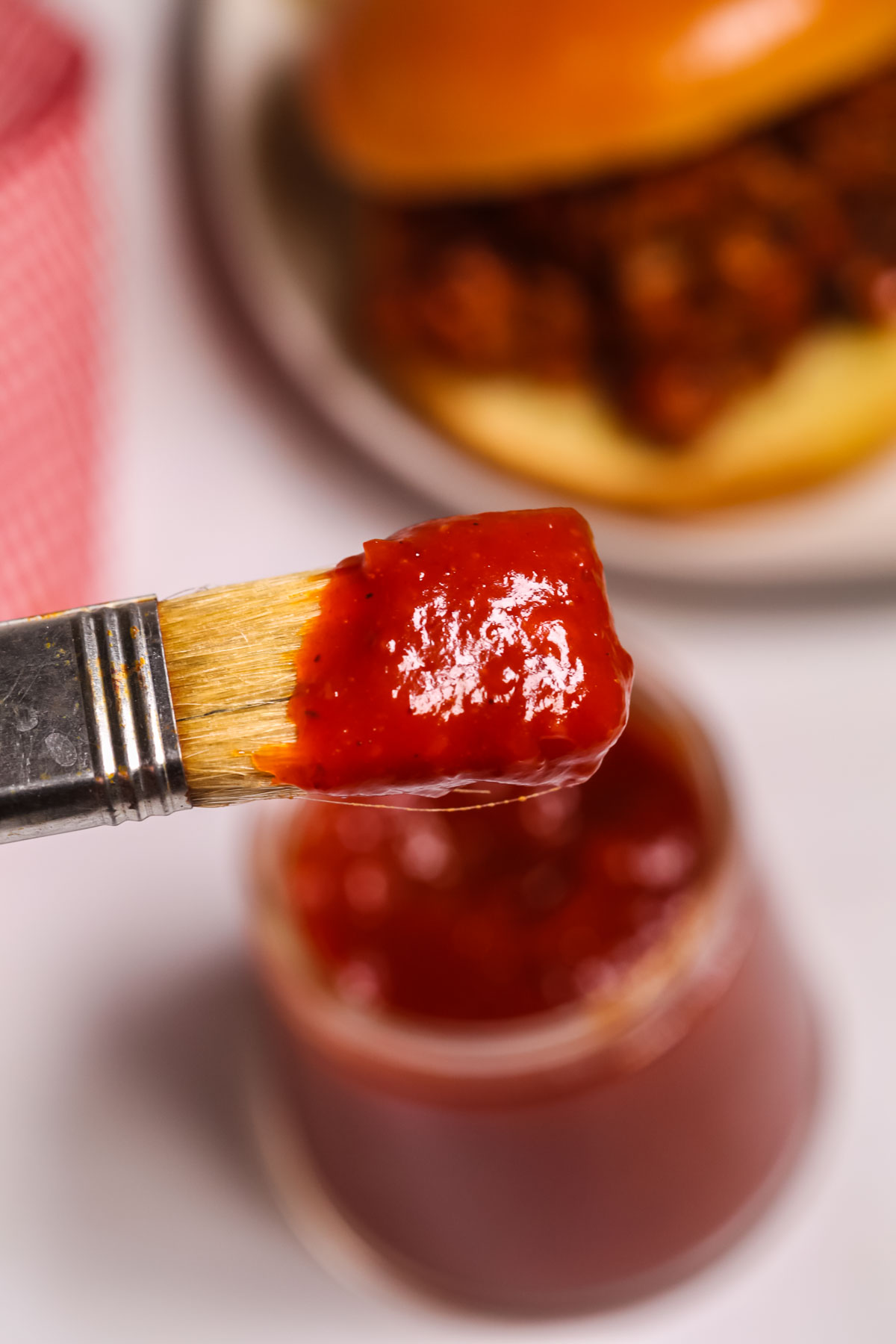 Close up of a brush scooping out the Chipotle Barbecue Sauce.