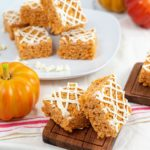Pumpkin Rice Krispie Treats on a wooden dish, and on a round plate and with a pumpkin.