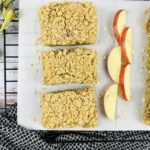 Three Apple Crisp Bars on a white plate with sliced apples.