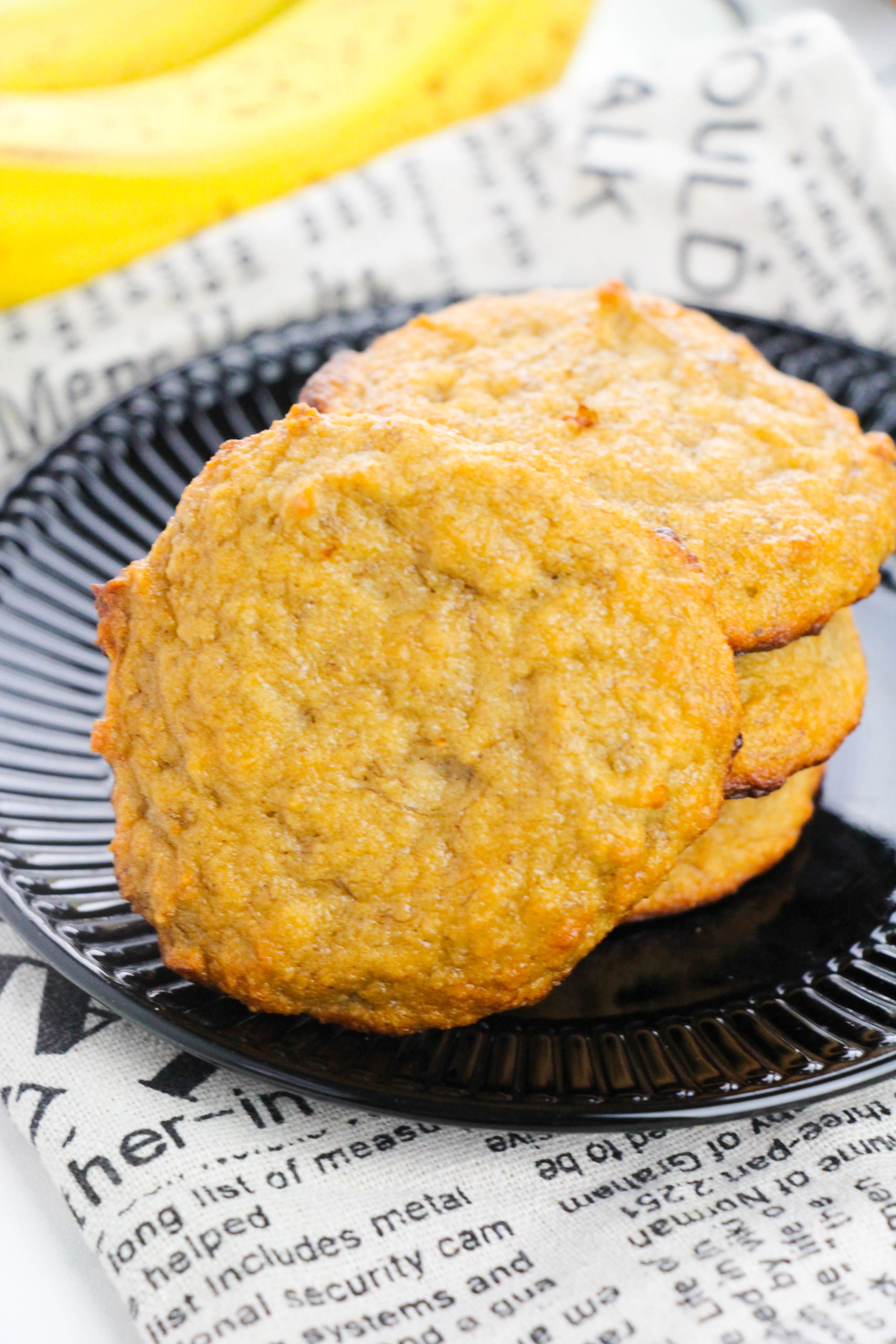 Stack of four banana bread cookies on a black plate with one laying on the side.