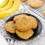 A stack of five banana bread cookies on a plate wih a bunch of bananas on the side.
