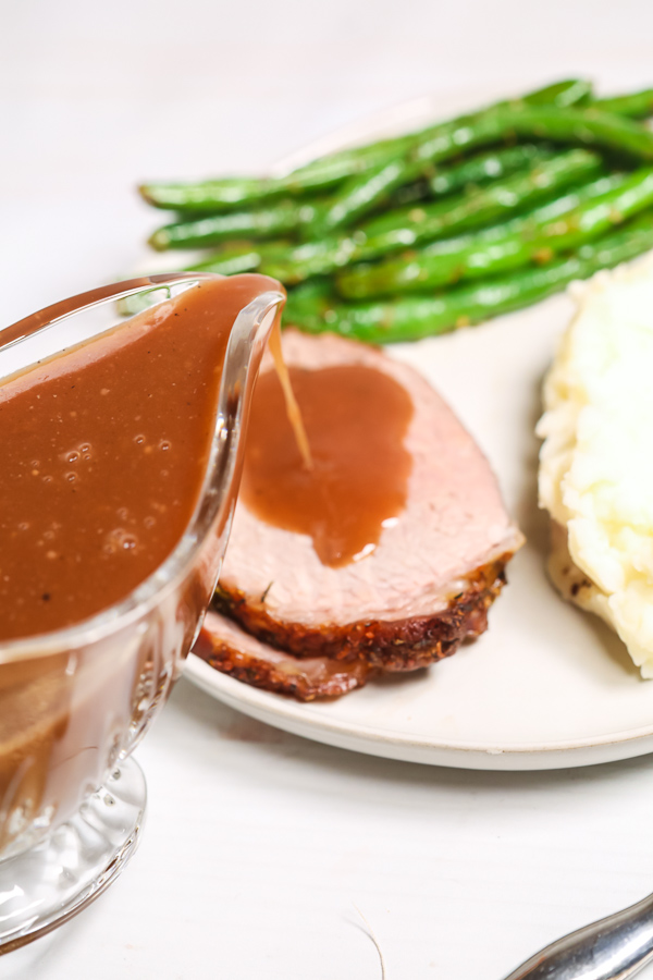 Slices of eye of round roast recipe on a plate with mashed potatoes and green beans with gravy drizzled on top.