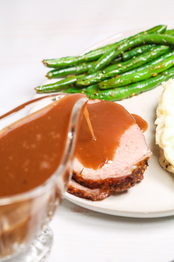 Beef with gravy being pored on it with side of green beans.