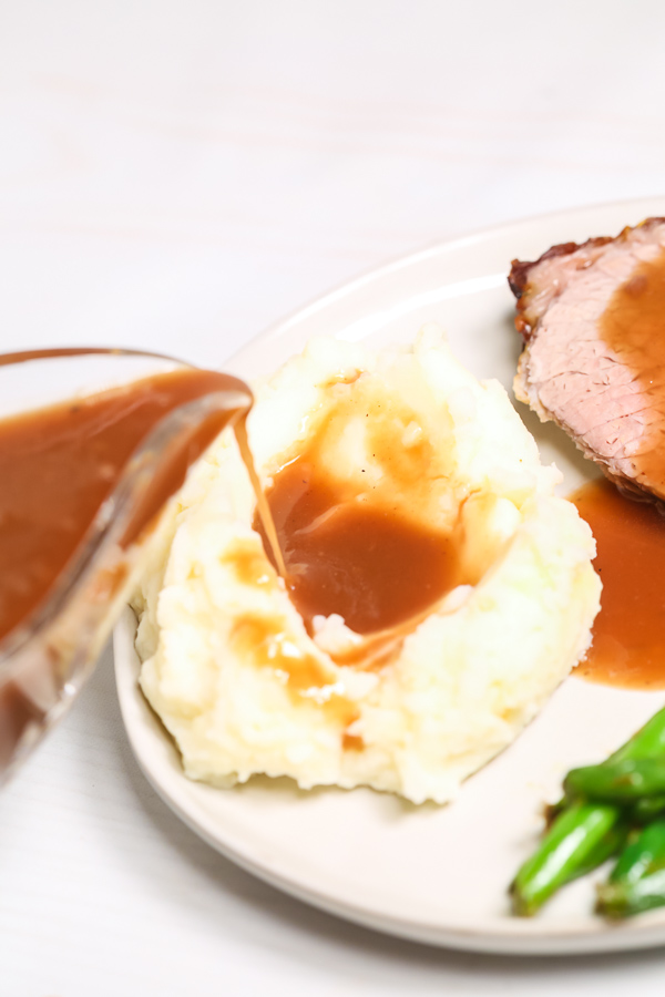 Beef Brown Gravy being poured on mashed potatoes.