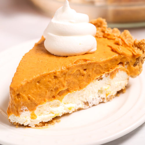 Double-Layer-Pumpkin-Pie on a white plate topped with whipped cream.