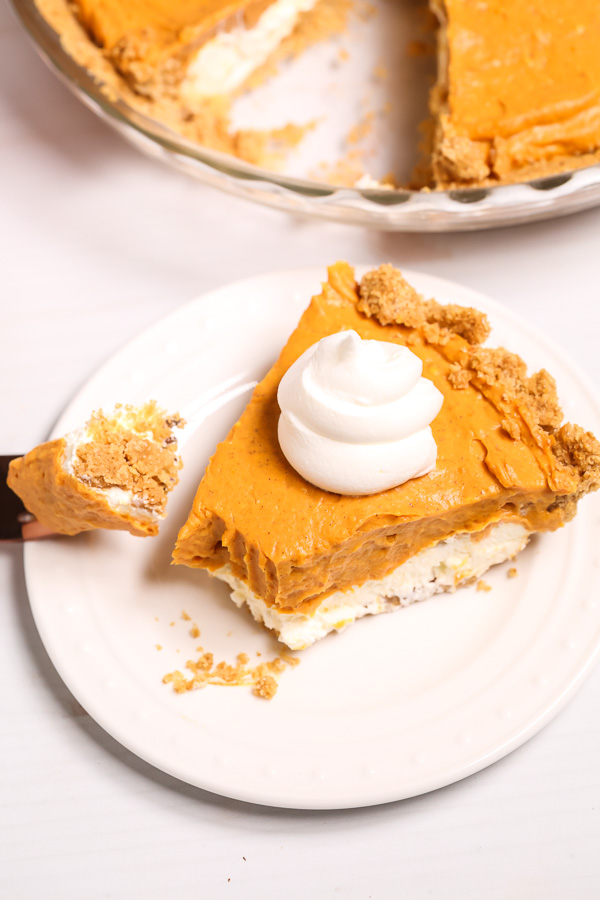 Double-Layer-Pumpkin-Pie with a bite taken out of it on a white plate
