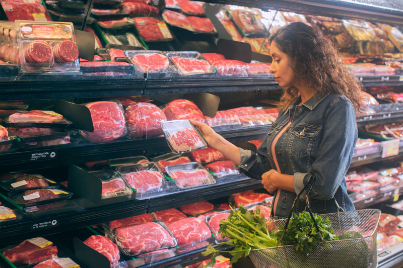 Woman looking at a steak in the grocery store.