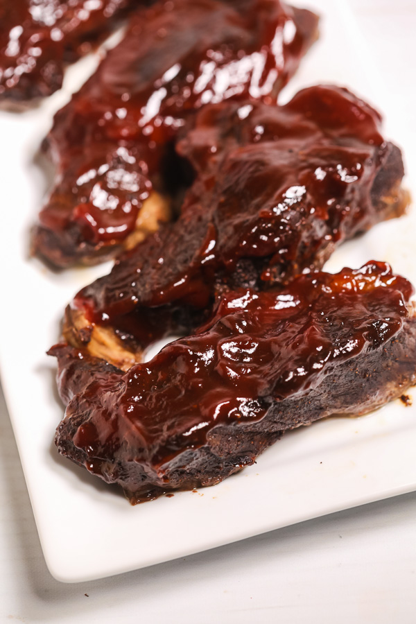 Country style ribs with BBQ sauce on a white plate.